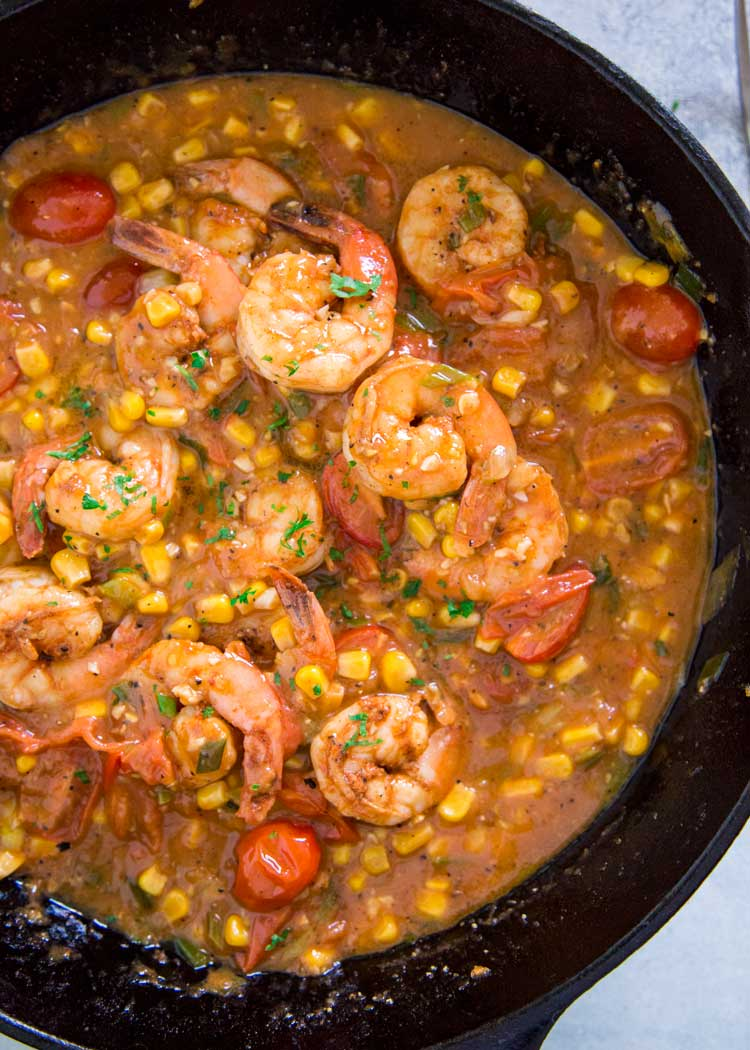 A traditional Southern dish, this Creole Shrimp and Grits is served in a well seasoned and spicy sauce with tomatoes and corn poured over cheesy grits. keviniscooking.com
