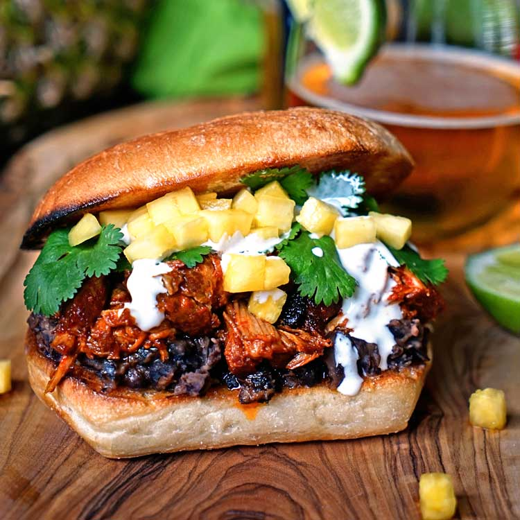 This slow simmered Pineapple Guajillo Chile Pulled Pork is stuffed in a ciabatta roll, layered on top of mashed black beans, a drizzle of Mexican crema, cilantro and diced pineapple. keviniscooking.com