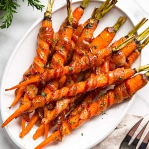These amazing Maple Glazed Carrots get bacon wrapped, sprinkled with black pepper and roasted, then basted with a maple Sriracha sauce. So easy and good! keviniscooking.com