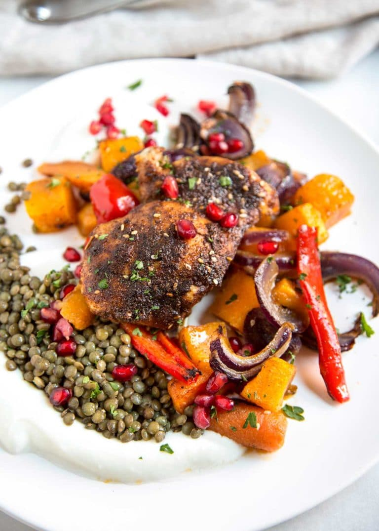 Moroccan Roasted Chicken starts with a rub of warm spices that include cinnamon, cumin, chili and mint. Roasted on top of fall vegetables all in one pan! keviniscooking.com
