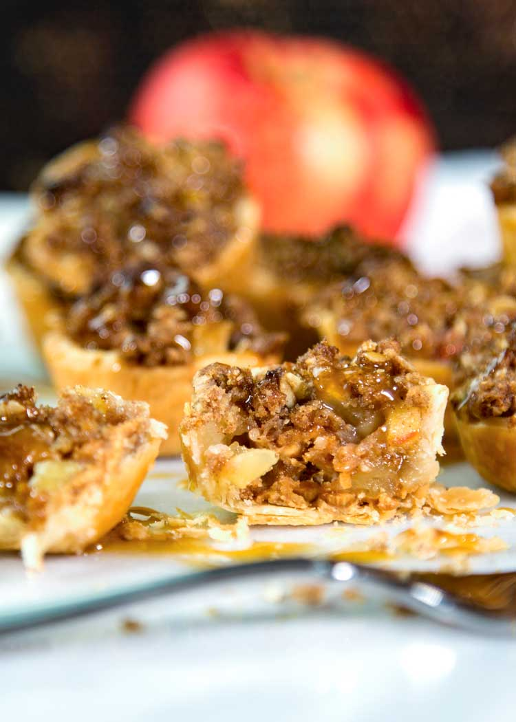 These Mini Peanut Butter Apple Pies have it all. Flakey pastry, peanut butter, diced apples, cinnamon and are topped with a crumb topping and caramel. keviniscooking.com