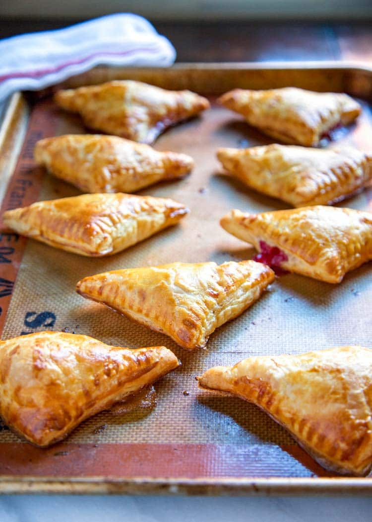 These tender Cranberry Brie Pastry Bites are super easy to make using puff pastry, dijon mustard, Brie cheese, cranberry sauce, or your favorite jam. keviniscooking.com