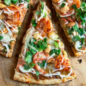 With a spicy peanut butter spread, this Thai Shrimp Pizza is loaded with crunchy vegetables, peppers, cheese and marinated shrimp. Baked or made on BBQ!! keviniscooking.com