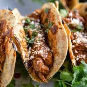 A mole is a Mexican sauce that is comprised of toasted nuts, dried fruit, chiles, chocolate and other savory ingredients, herbs and spices. Typically simmered for hours, my Instant Pot Chicken Mole Tacos are made in under an hour… and they're amazing!