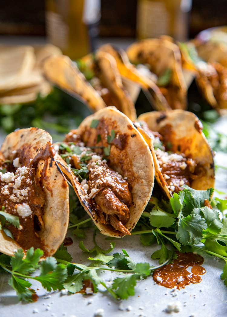 mole chicken tacos and cilantro on a counter