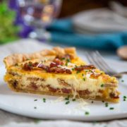 Let me show you How to Make Quiche Lorraine, the Queen of all quiches. A delicious egg custard seasoned with nutmeg gets poured over shallots sautéed with bacon and herbs in a tender, flaky pastry crust. Baked until just set and served warm for the perfect brunch or lunch meal.
