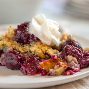 plate of cherry crisp with whipped cream