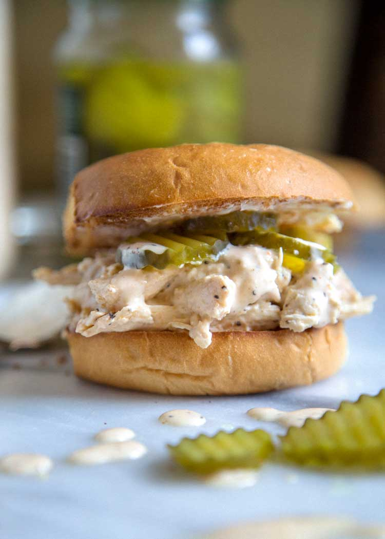 close up of a shredded chicken sandwich with pickles