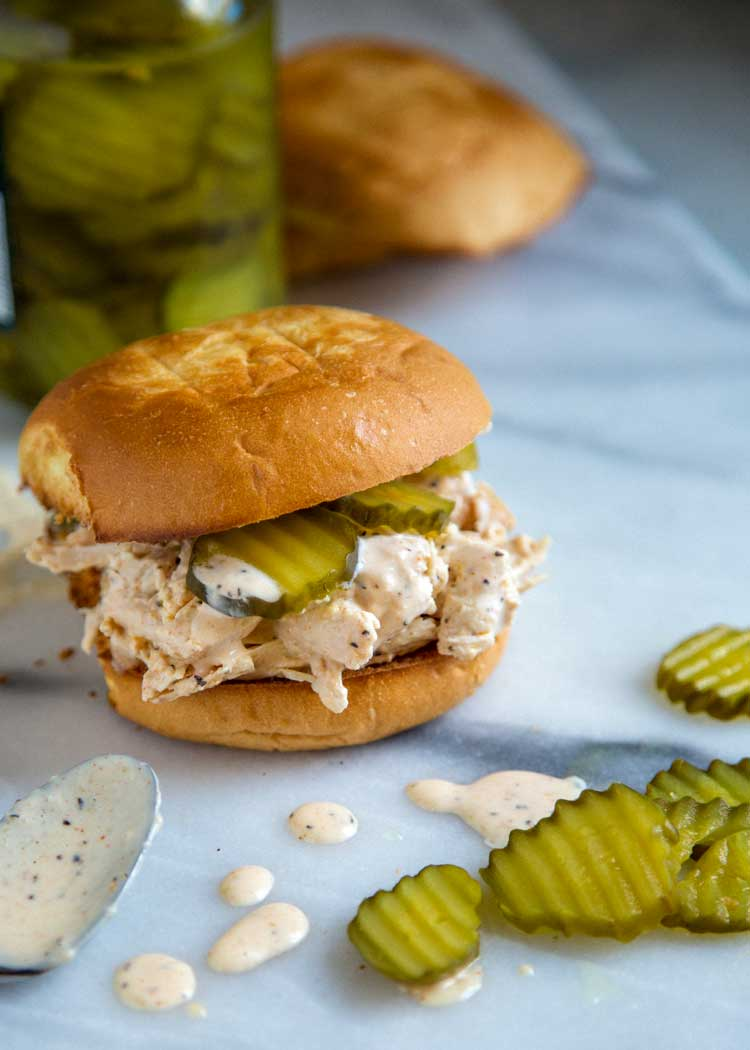 chicken and pickles with white sauce on a toasted bun