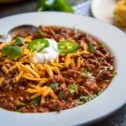 This here is real deal Chili Con Carne! Made with chopped beef chuck, ground pork and a puree of soaked ancho and guajillo chiles, garlic, cumin, and other spices that simmers and thickens for a perfect Tex Mex chili meal.