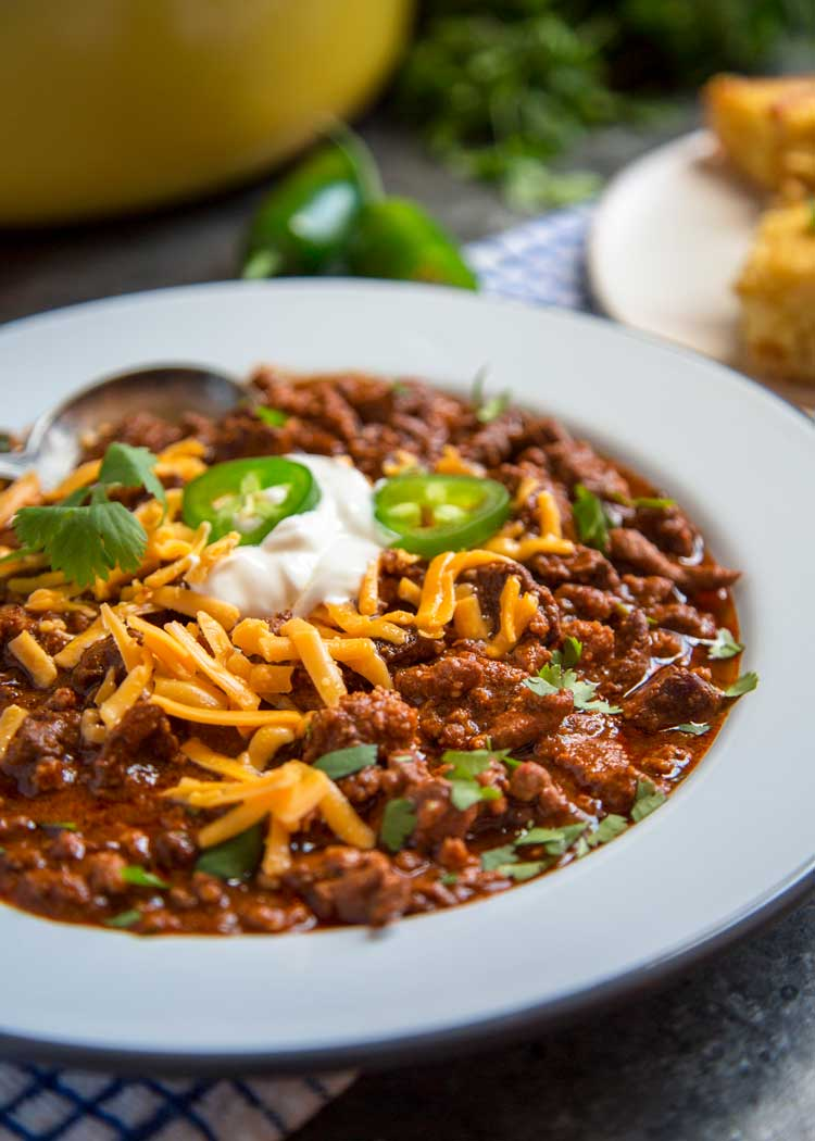 bowl of beef and pork chili in a white bowl with shredded cheddar, sour cream, and jalapenos on top