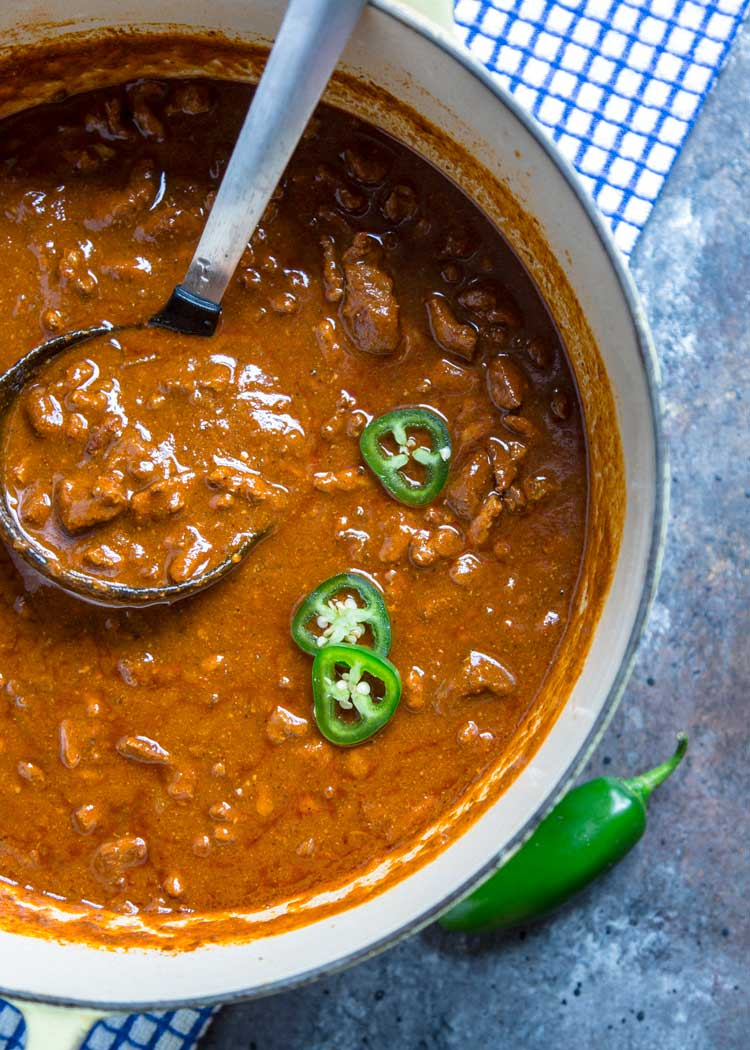 ladling thick, hearty beef chuck chili from a large pot