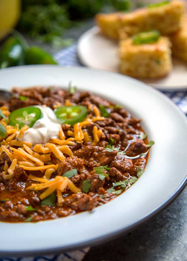 serving of Tex-Mex Chili Con Carne topped with shredded cheddar and jalapeno slices in a white bowl