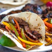 A Tex Mex favorite and staple at many restaurants, Grilled Steak Fajitas are the perfect blend of well seasoned steak charred with bell peppers and onions all wrapped in a warm tortilla.