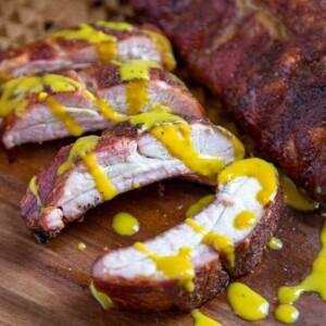 A close up of South Carolina pork ribs with mustard sauce