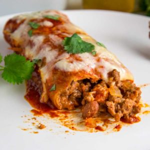 cheese melted on top of a beef and bean enchilada