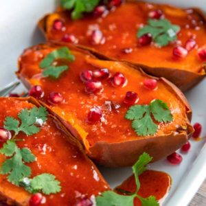 A plate of sweet potatoes with honey butter glaze and pomegranate