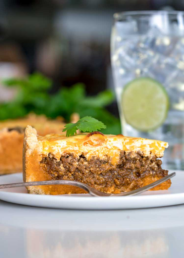 slice of Beefy Taco Pie on white plate with glass of water