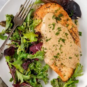 A plate of salad and a fork, with Chicken and creamy roasted Garlic sauce