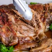close up of tongs pulling tender rosted leg of lamb
