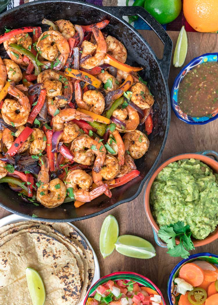 skillet of shrimp fajitas with guacamole salsa and pickled carrots