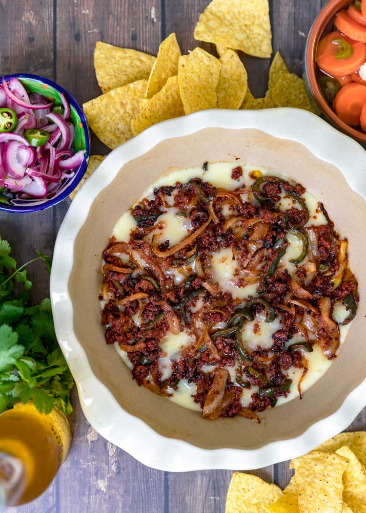 overhead shot of Queso Fundido in a pie dish with chips