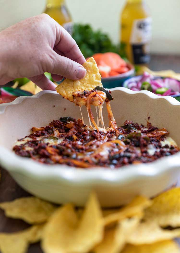 tortilla chip scooping cheesy chorizo dip