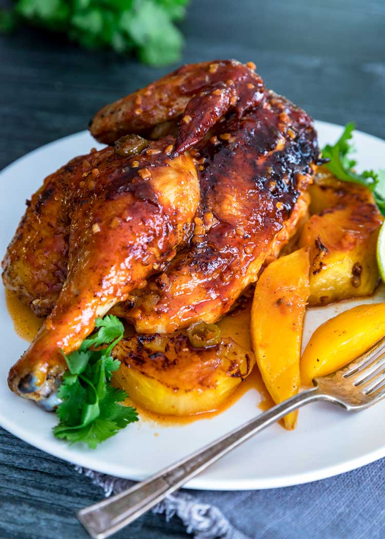 close up of half Tropical Roasted Chicken with fruit on white plate