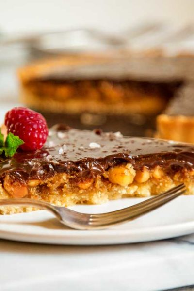 slice of macadamia nut tart with chocolate ganache topping