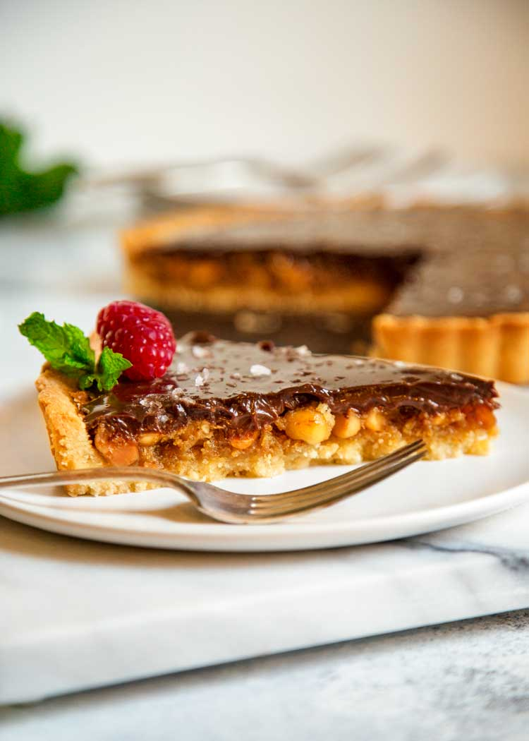 slice of macadamia nut tart with chocolate ganache topping