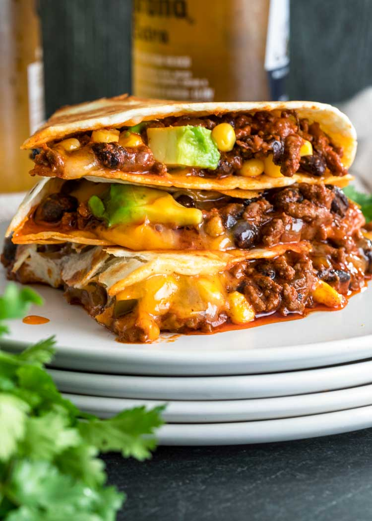 stack of Crispy Ground Beef Quesadillas on white plate with beer