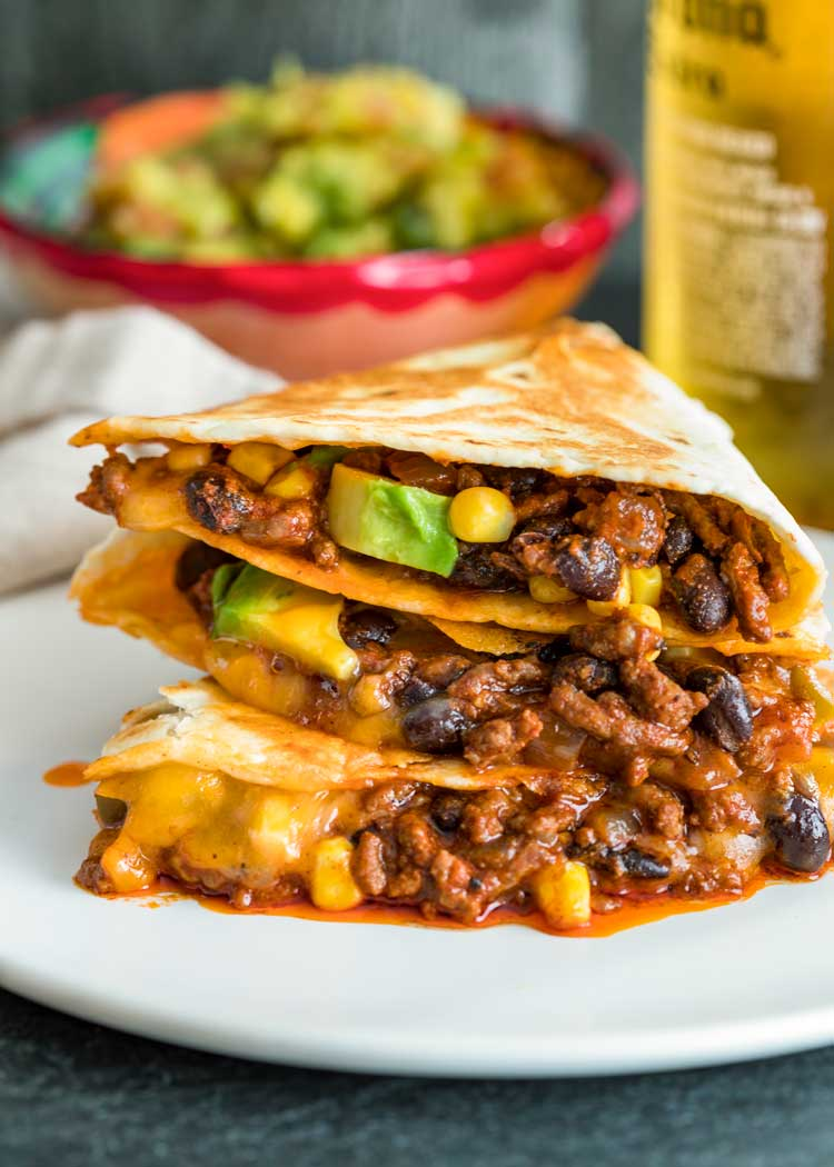 stacked crispy ground beef quesadillas on white plate with guacamole