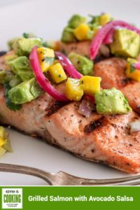 two grilled salmon filets topped avocado salsa on a white plate #salmon #grilled #salsa #avocado