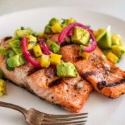 two grilled salmon filets topped avocado salsa on a white plate