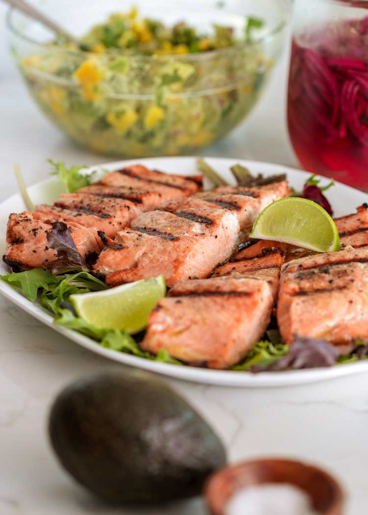 grilled salmon filets on white platter