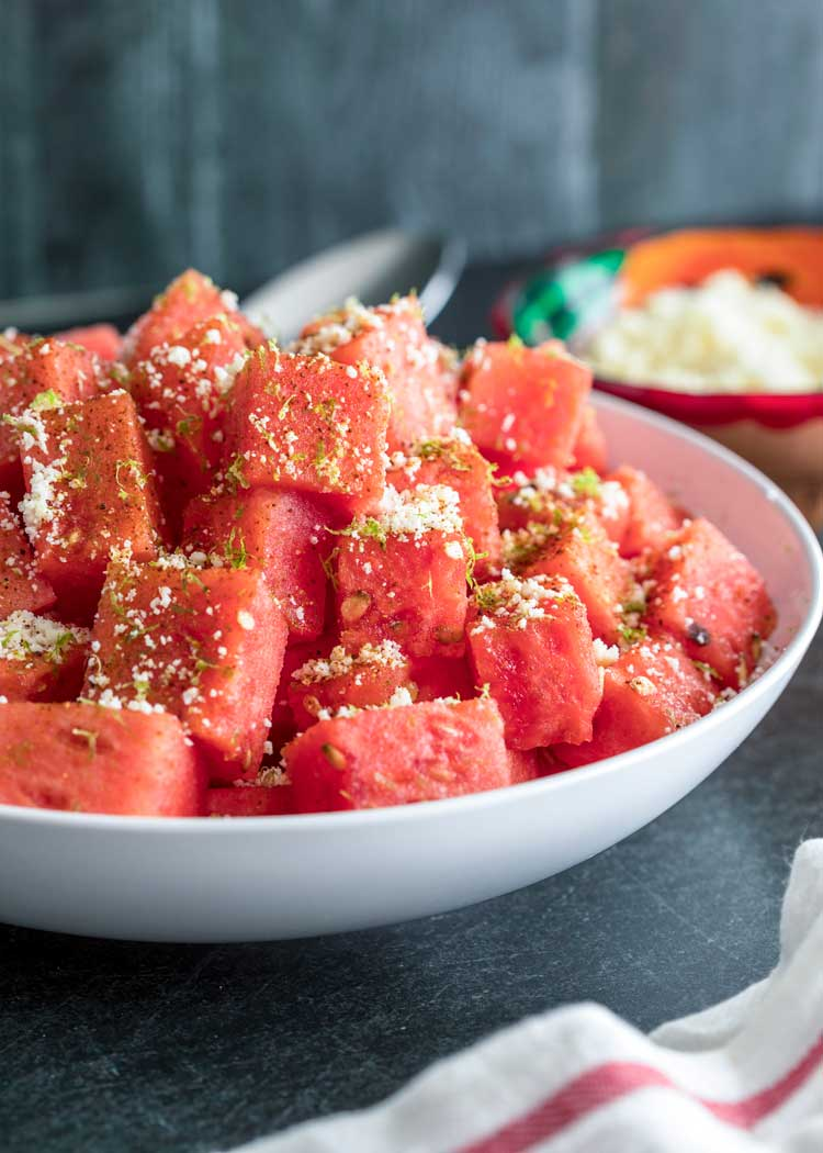 watermelon salad with cheese lime and chili powder in a white bowl