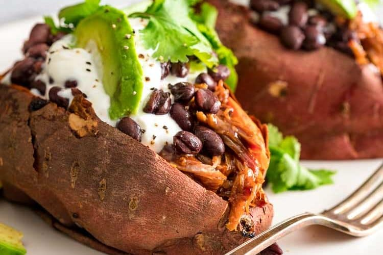 close up of 2 Pulled Pork Stuffed Sweet Potatoes on a white plate