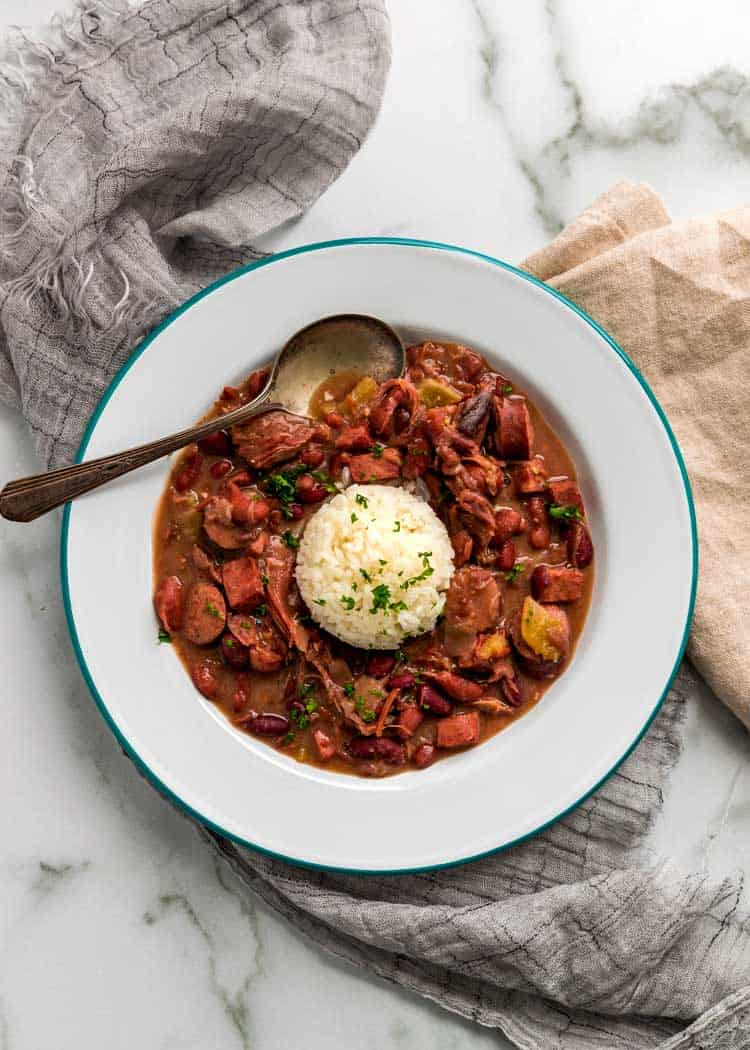 overhead: spoon in white bowl of instant pot red beans and rice