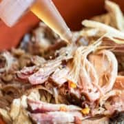 squirting North Carolina BBQ Sauce on pulled pork from bottle