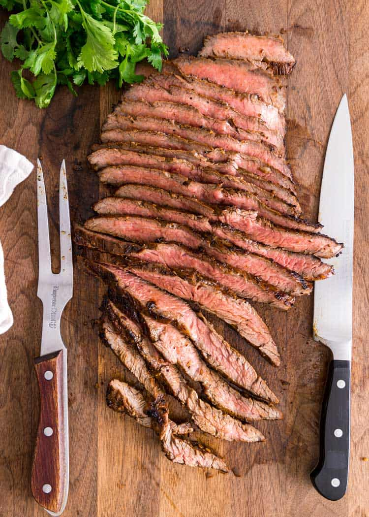 overhead shot of sliced flank steak on wooden board