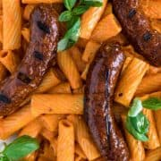 grilled sausage on pasta with basil leaves