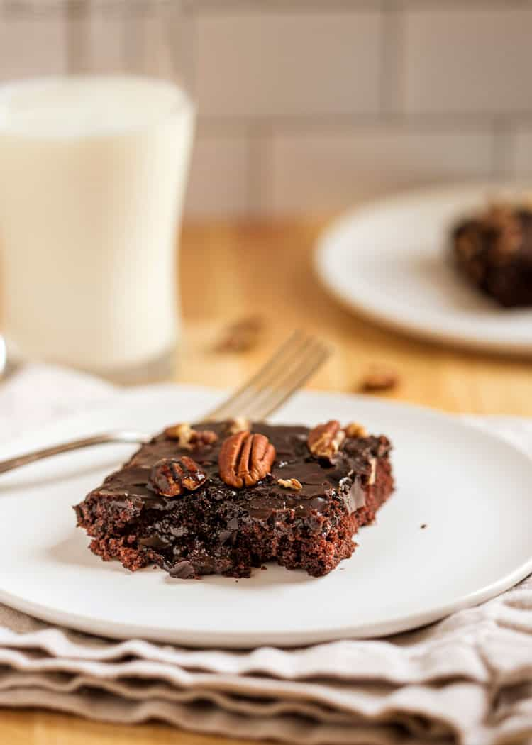 chocolate Cake on white plate with fork and glass of milk