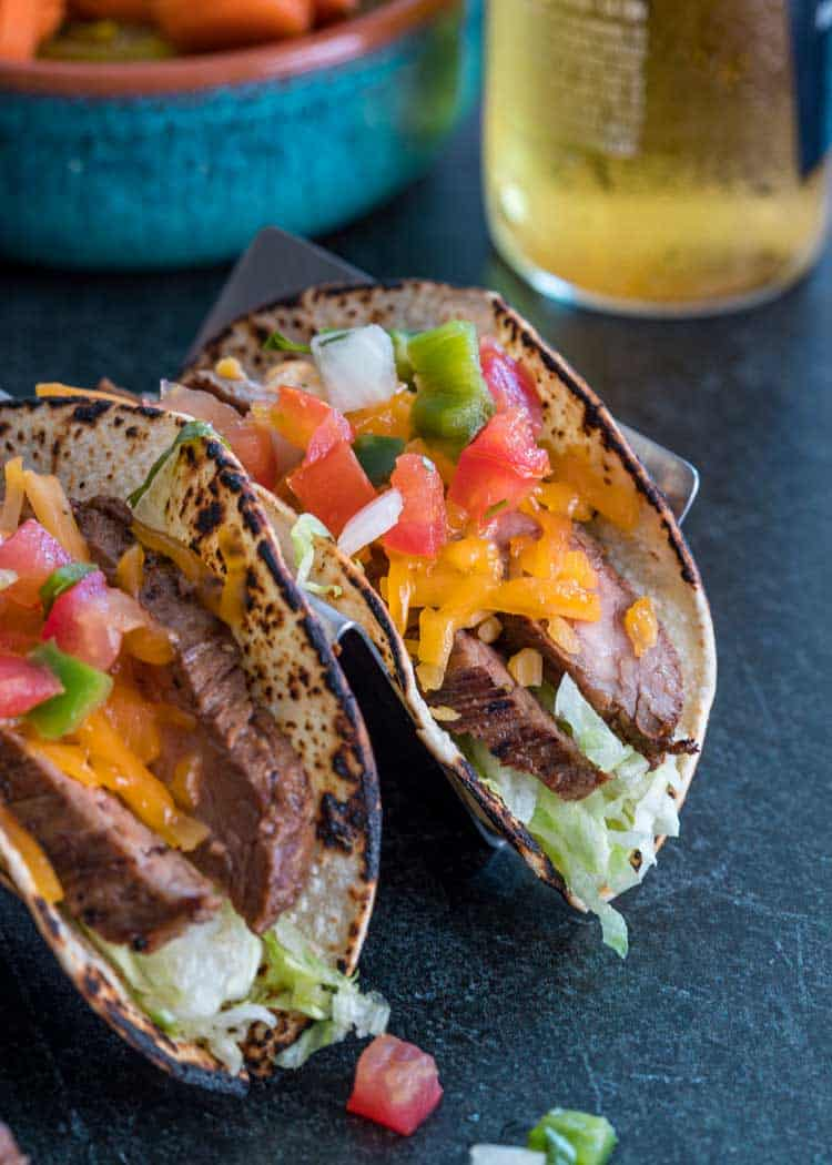 Flank Steak Tacos with shredded cheese and pico de gallo