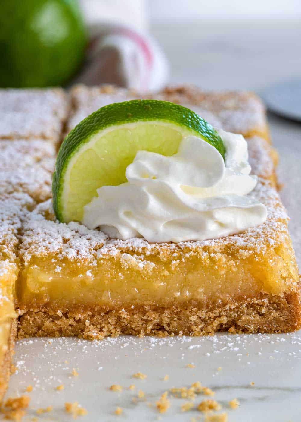 key lime bar with whipped cream and lime slice