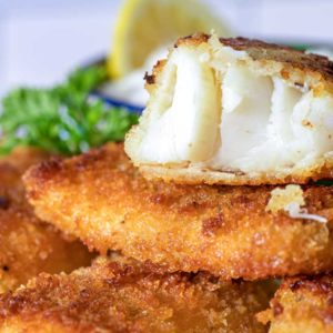 A close up of baked fish sticks with lemon