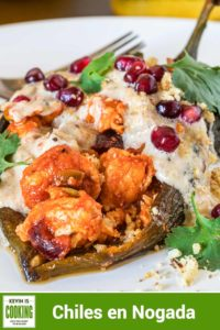 Chiles en Nogada are roasted poblano chiles stuffed with chicken, vegetables and fruit, topped with a walnut cream sauce, pomegranate arils and cilantro. #chiles #stuffed #Mexican