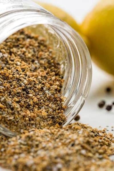 close up of Lemon Pepper Seasoning tipped over in glass jar