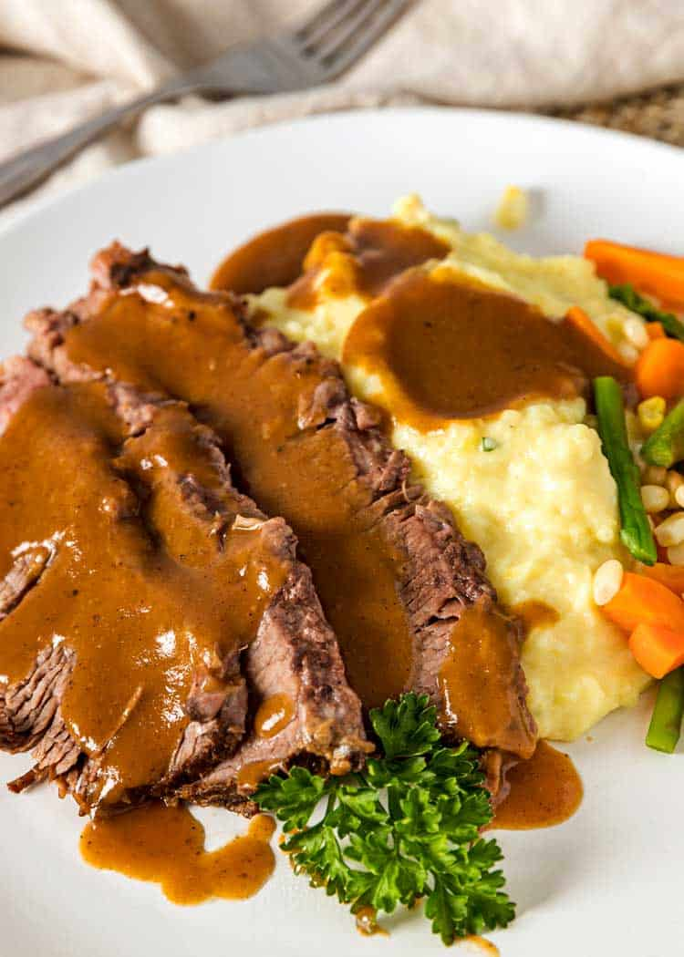 sliced Yankee Pot Roast with gravy, mashed potatoes and steamed vegetables