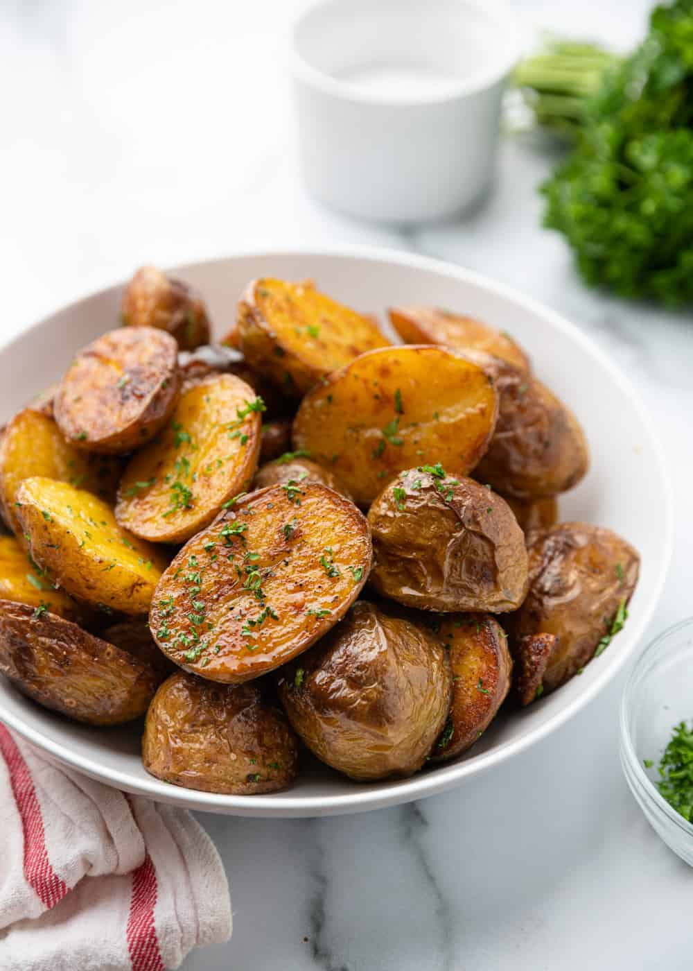 oven roasted potatoes in white bowl with parsley