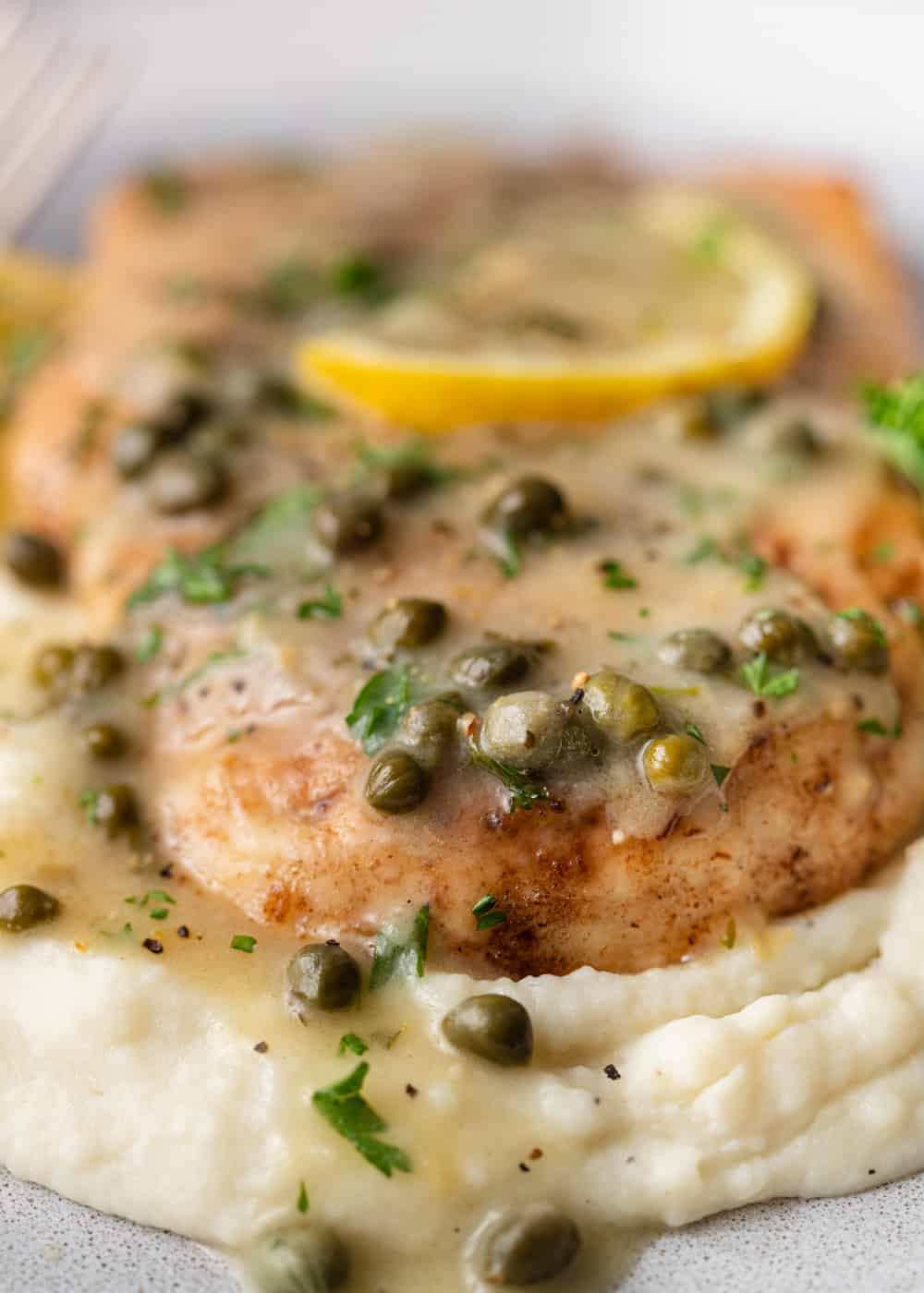 close up of chicken piccata on mashed potatoes